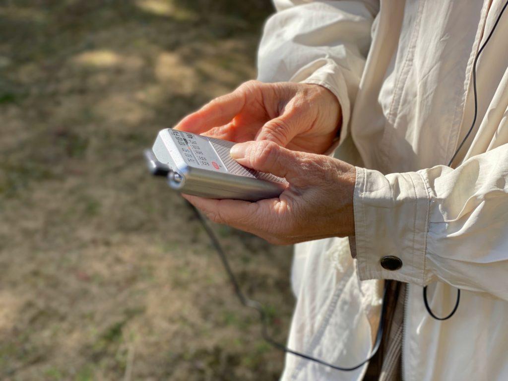 屋外でラジオを聴く高齢者